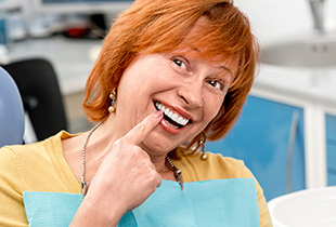 Senior woman pointing toward tooth
